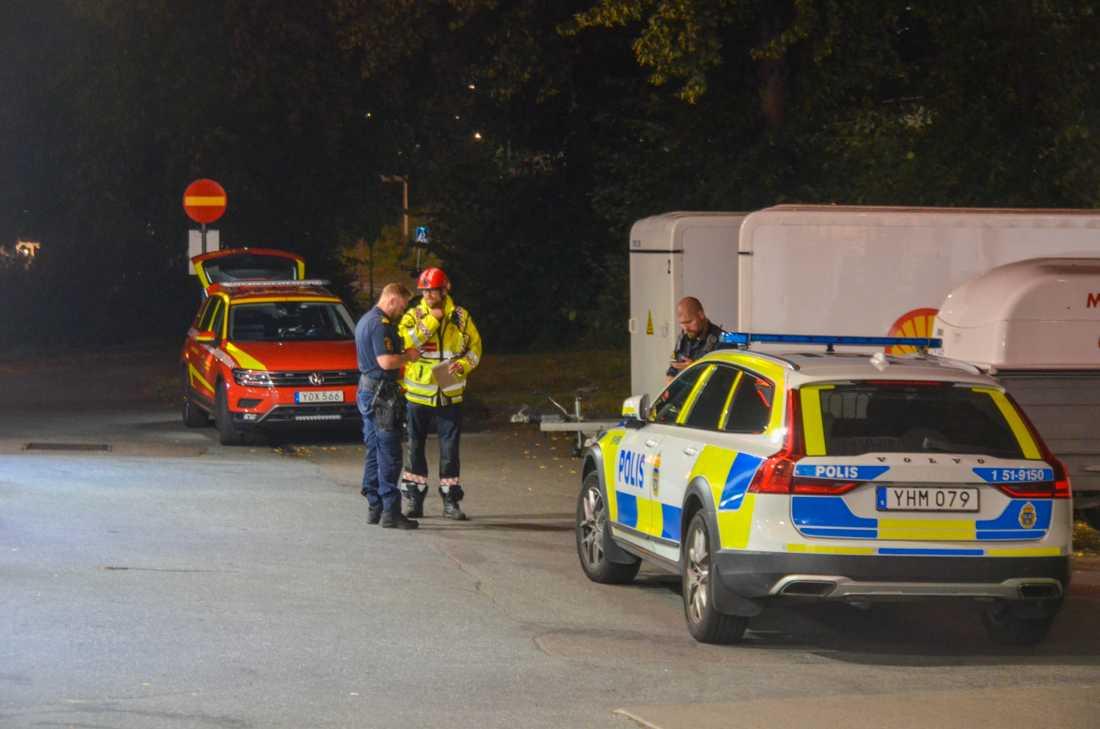 Polisen samtalar med räddningstjänsten utanför avspärrningarna.