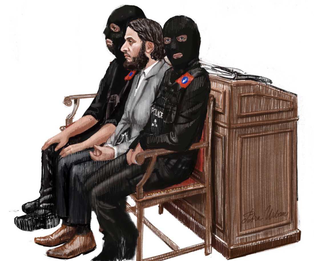 Salah Abdeslam mellan två maskerade poliser på en teckning från rättegången i början av februari. Arkivbild.