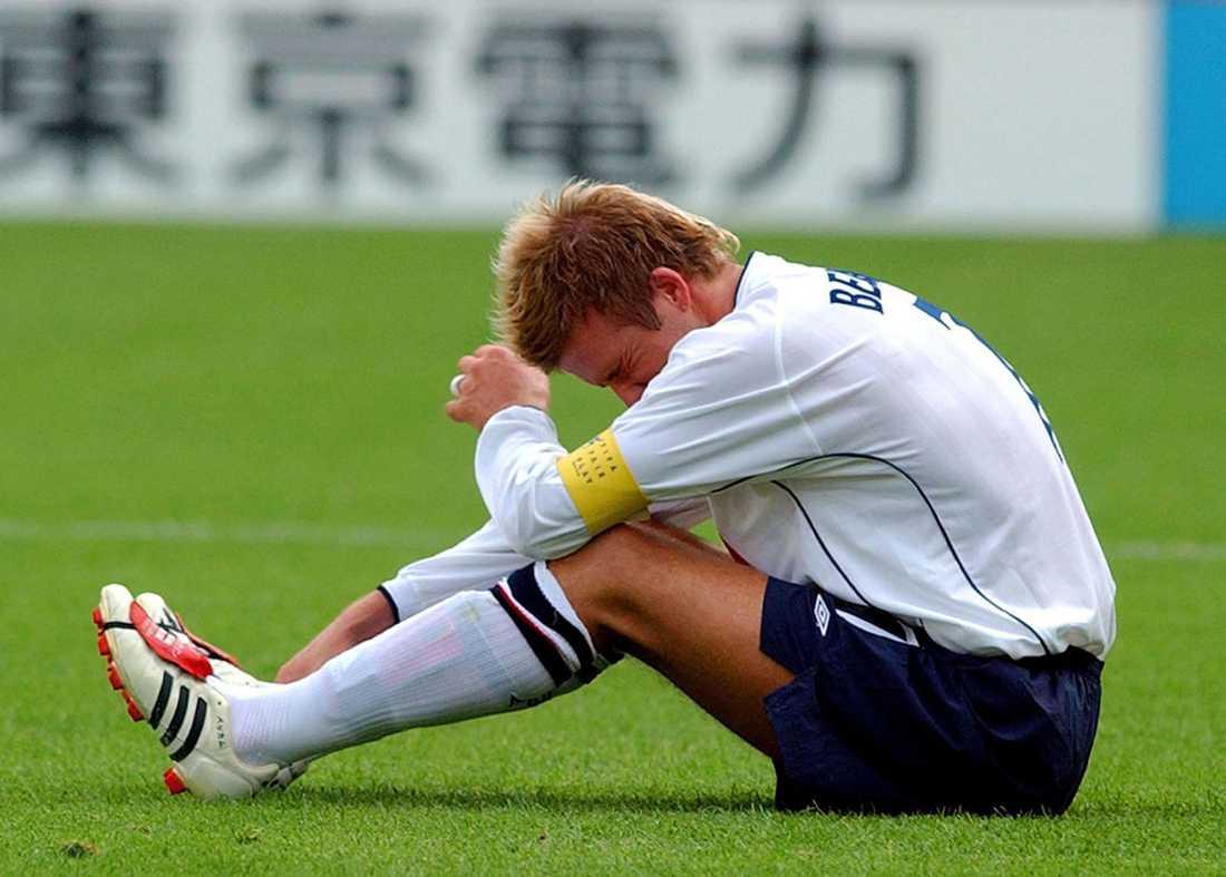 England förlorade VM-kvartsfinalen mot Brasilien i juni 2002 med 1-2. David Beckham har ont av flera anledningar.