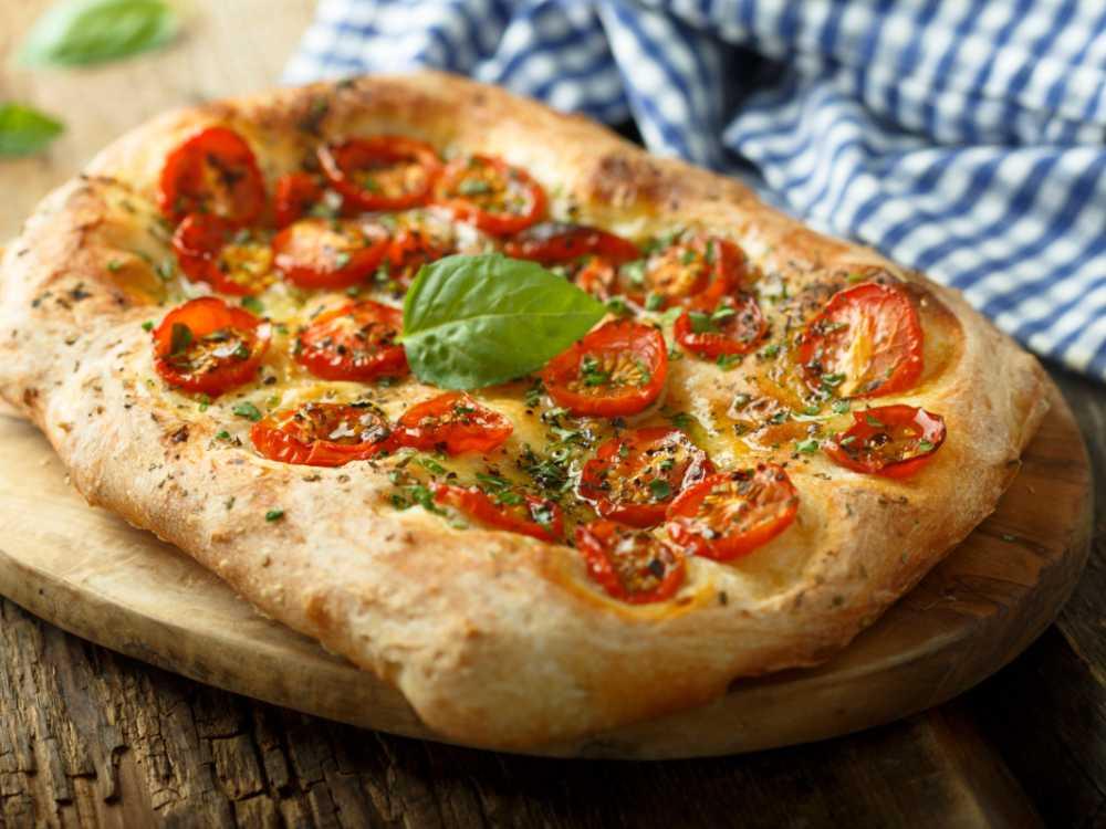 Härligt mjuk, nybakad focaccia toppade med tomater och basilika.
