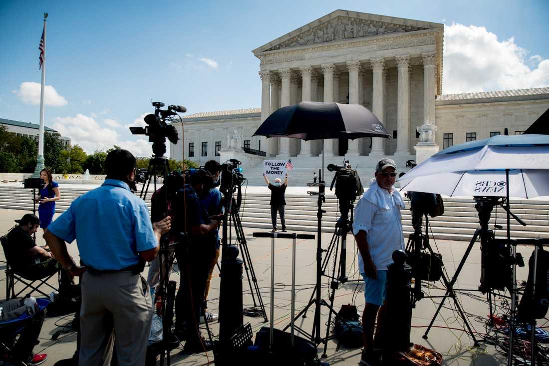 """En demonstrant utanför USA:s högsta domstol håller upp en skylt med texten """"Följ pengarna""""."""