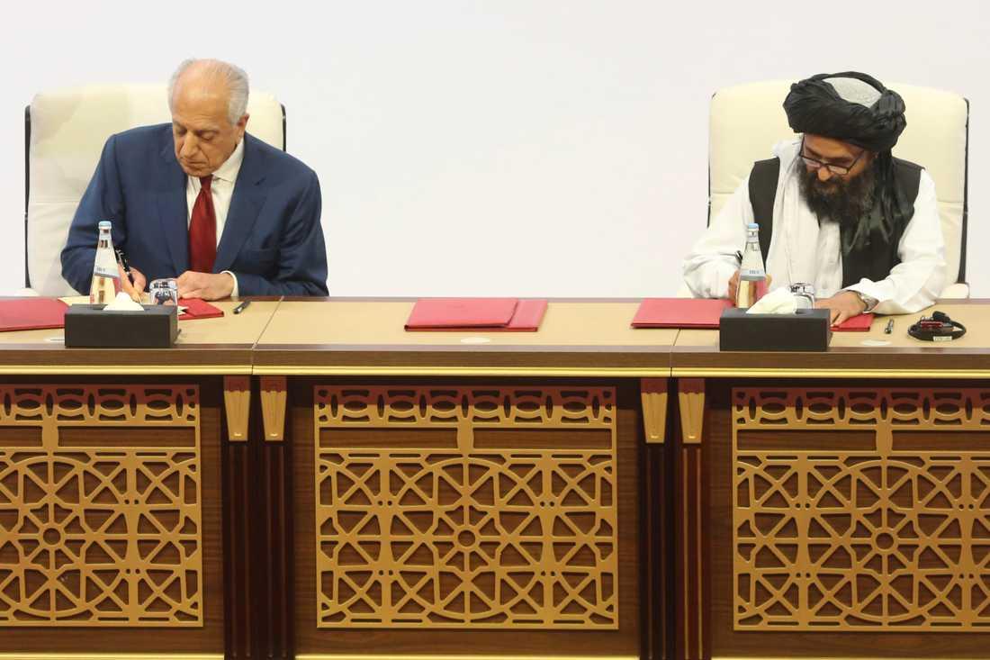 USA:s särskilde sändebud Zalmay Khalilzad och talibanrörelsens chefsförhandlare Abdul Ghani Baradar skakar hand efter att ha undertecknat ett avtal mellan parterna i Doha i Qatar den 29 februari.