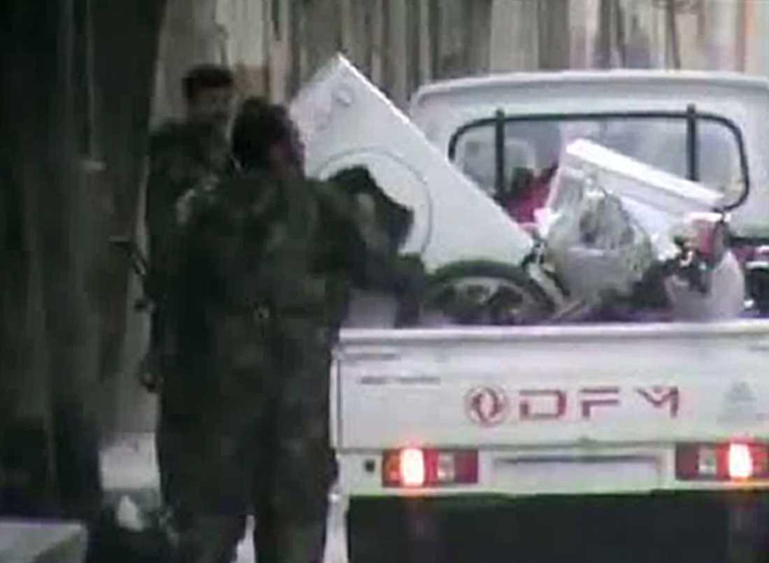 Syriska säkerhetsstyrkor plundrar hem i staden Homs.