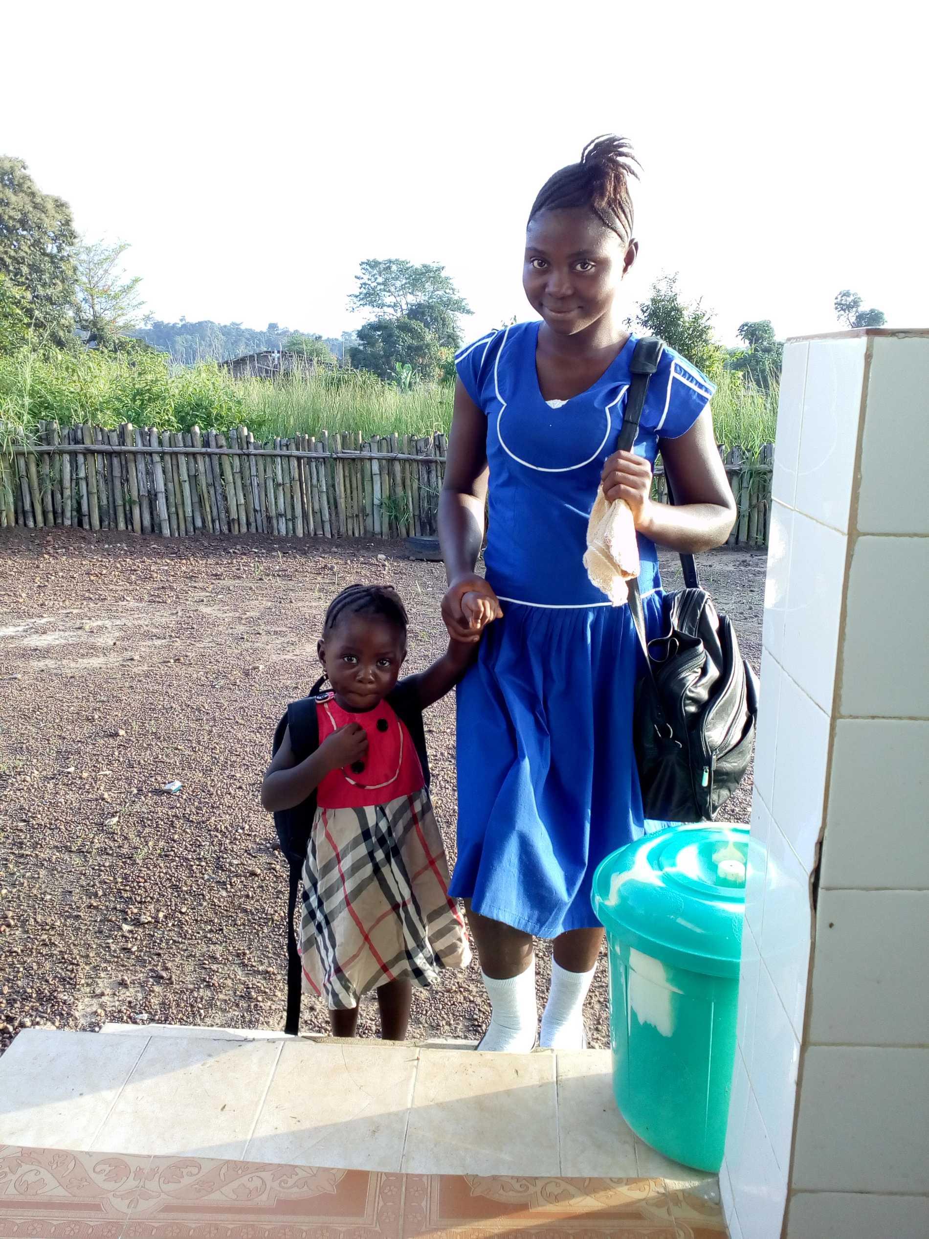 Lombeh M Sillah med sin dotter Anointina. Dottern är på daghem medan Lombeh är i skolan.