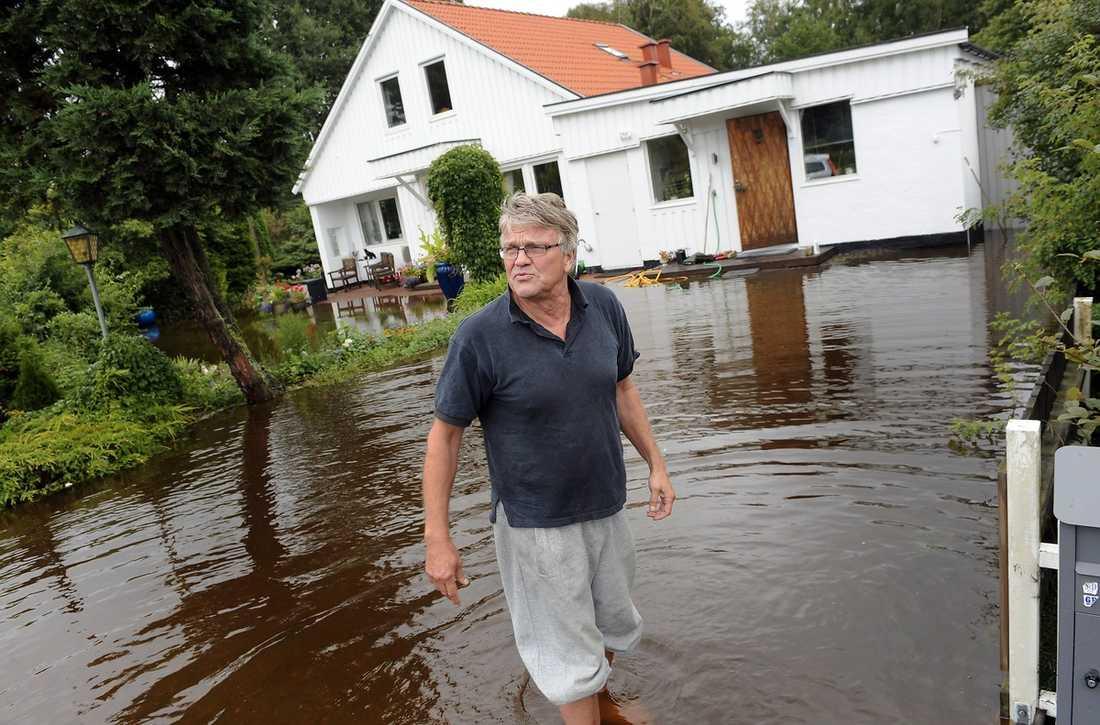 ÖVERSVÄMMAD TRÄDGÅRD Gunnar Frånberg fick hela trädgården under vattenytan och vattnet tog sig in i vardagsrummet. Men eftersom hans hus ligger på enskild väg fick han ingen pumphjälp av räddningstjänsten. Foto: ROGER LUNDSTEN