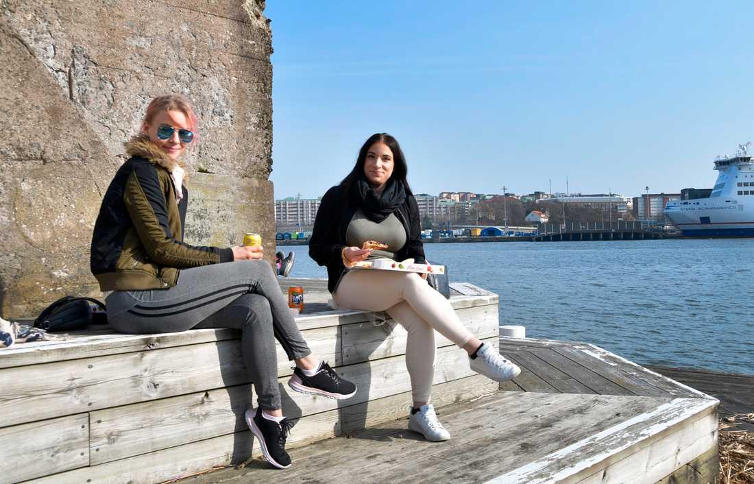Josephine Lindström och Madelene Lundqvist njuter en veganpizza på kajkanten på Eriksberg, Göteborg.
