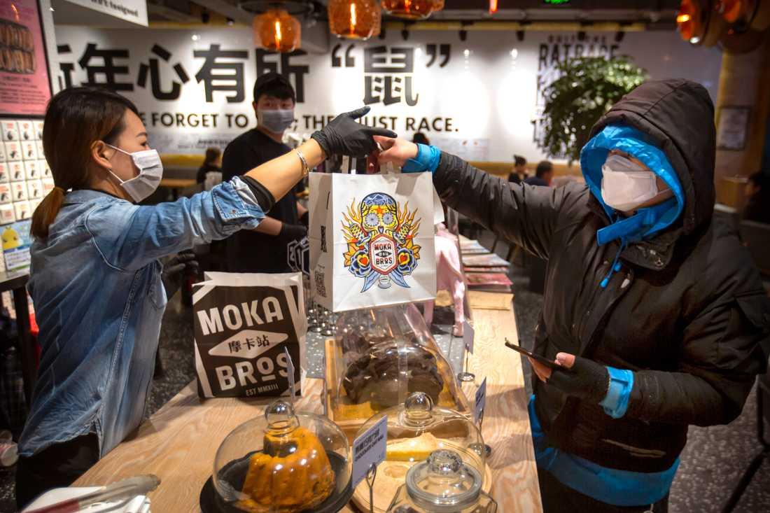 Chen Tiantian lämnar över mat för hemleverans vid ett kafé i Peking. I påsen fanns förutom maten även en lapp med temperaturen på kocken som tillagat den.