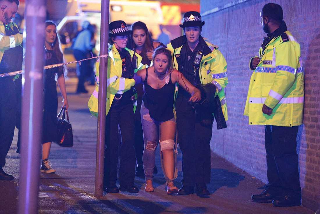 En skadad kvinna hjälps ut från Manchester Arena efter attacken.