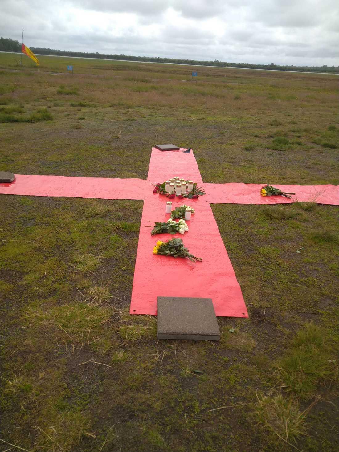 Sörjande har placerat blommor på ett stort kryss som fallskärmshoppare siktar på under hoppen.