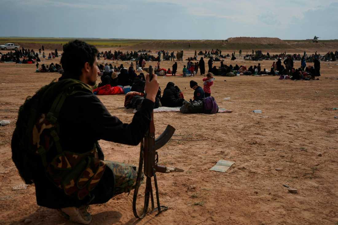 En medlem i den kurdisk-arabiska milisen SDF vaktar människor som strömmat ut från IS-enklaven vid staden al-Baghuz i sydöstra Syrien.