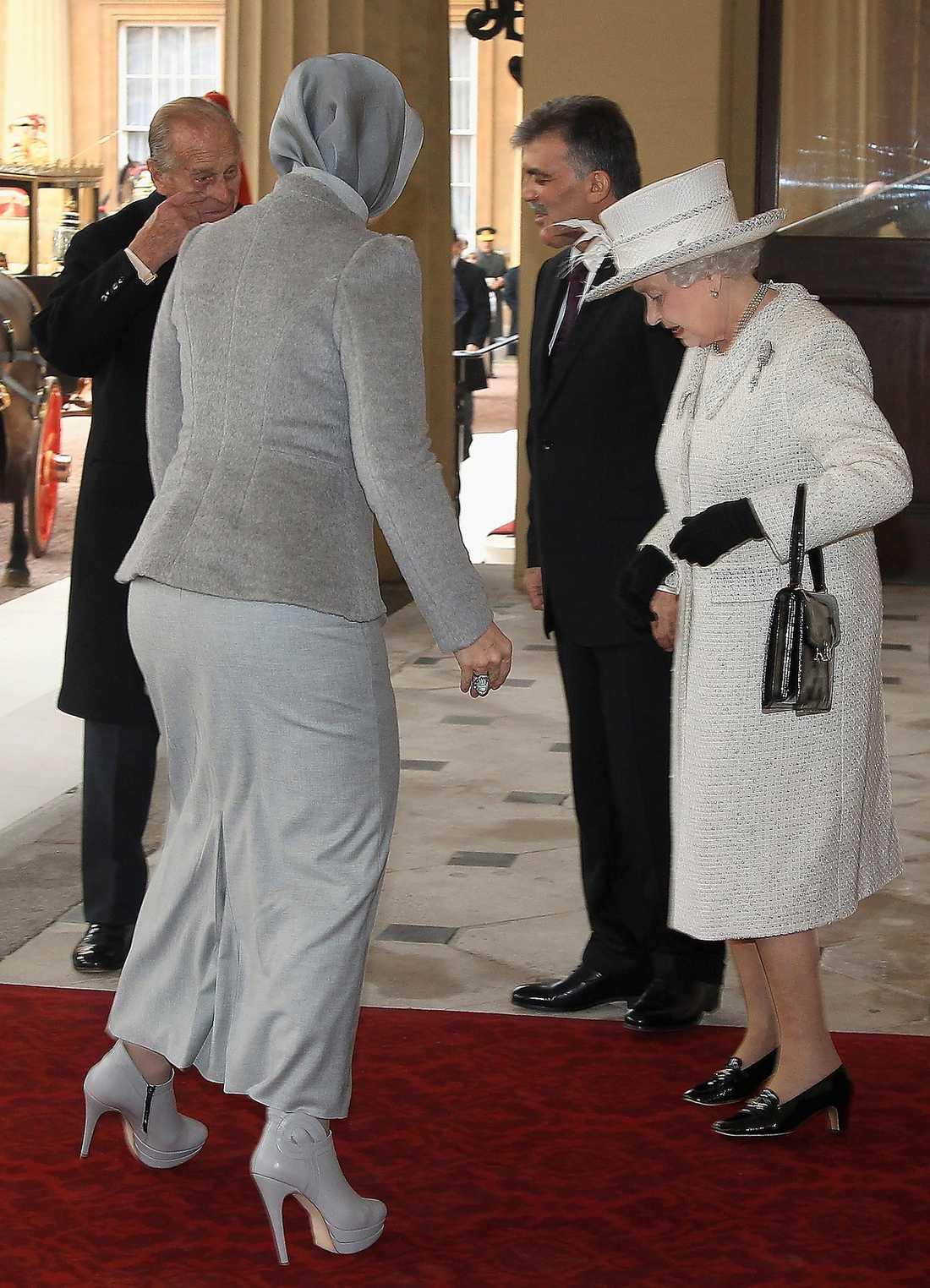 Drottning Elizabeth studerar Turkiets första dam Hayrunnisa Guls skor under ett besök i Buckingham Palace.