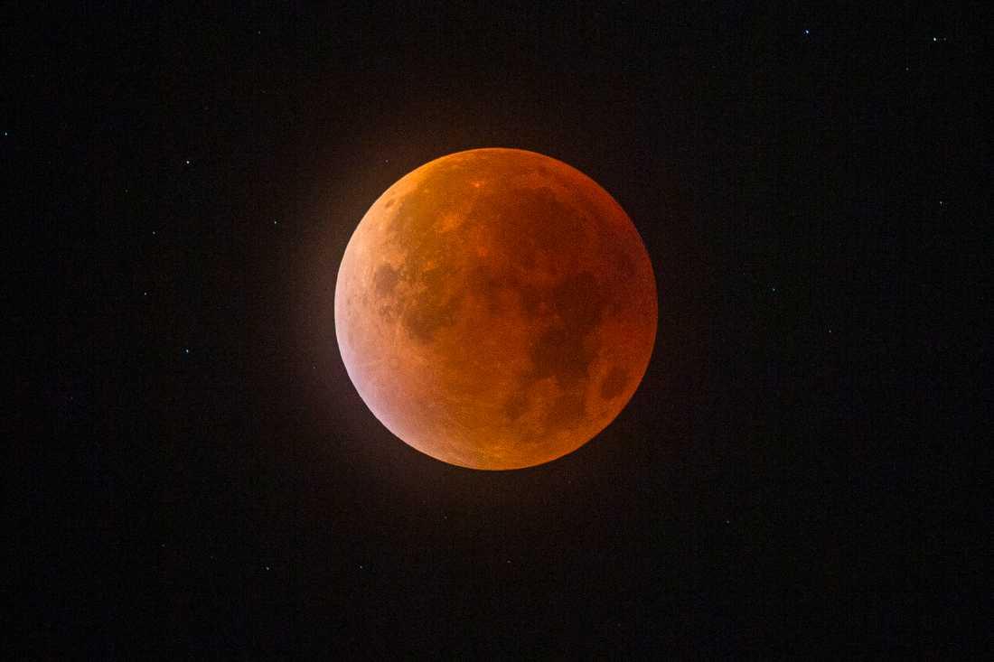 När solens strålar träffar månen genom jordens atmosfär färgas månen röd. Arkivbild.