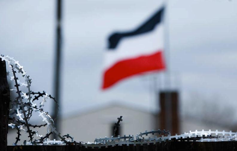 Nationalflaggan för det tyska riket mellan 1871 och 1918 svajar i luften bakom ett ståltrådsstängsel som skyddar högerpartiet NPD:s lokaler i staden.