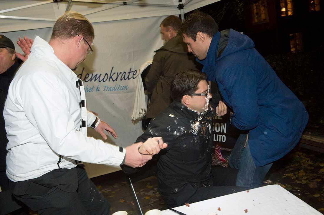 Jimmie Åkesson får en tårta i ansiktet under en boksignering, vid Nytorget i Stockholm.