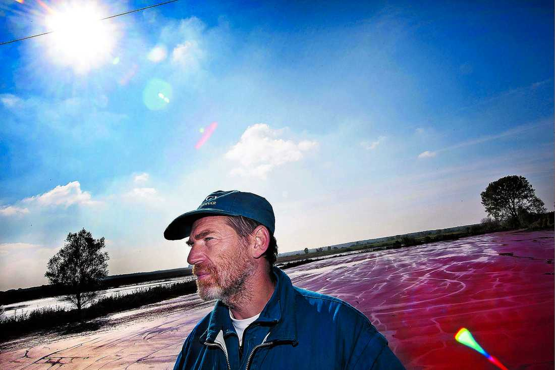 """HÄR BADADE BARNEN Ingenjören László Kovács, 49, blickar ut över floden Torna och de omgivande åkrarna som täcks av den frätande gyttjan. """"Jag är pensionär innan vi fått ordning på det här."""""""