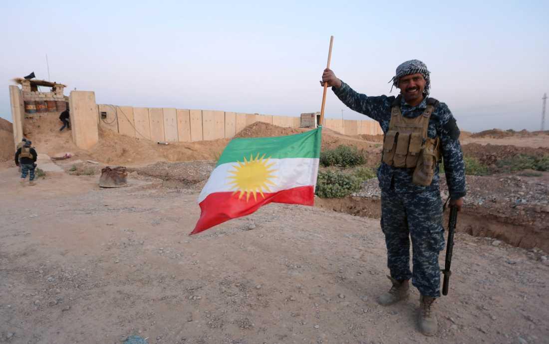 En irakisk soldat håller en upp-och-nedvänd flagga.