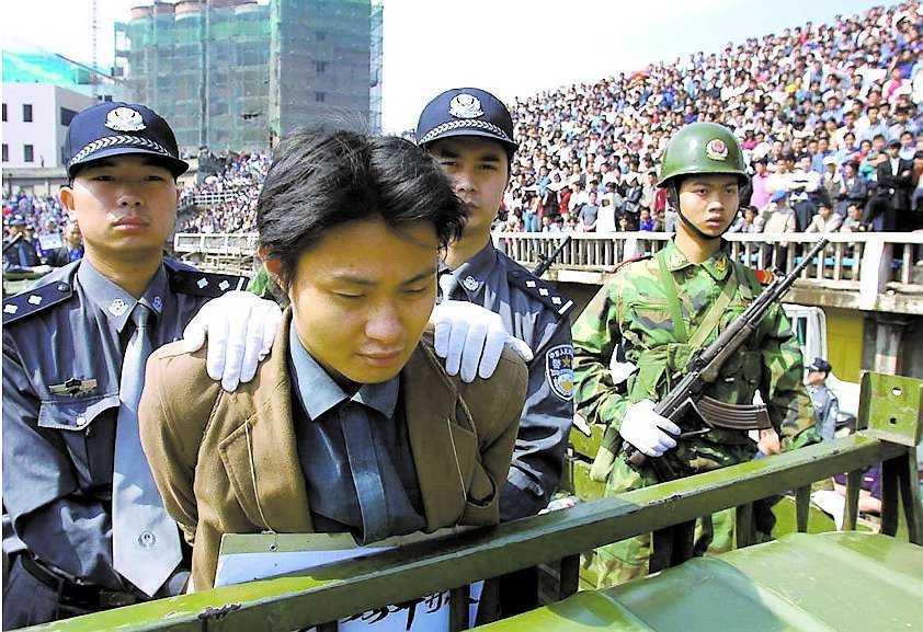 EN ANNAN ARENA Den här fången har dömts till döden för rån och mord. Här förs han runt arenan vid ett massmöte i Chengdu år 2001.