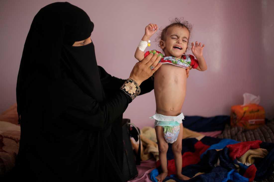 En kvinna i Jemen håller upp sin undernärda son. Arkivbild
