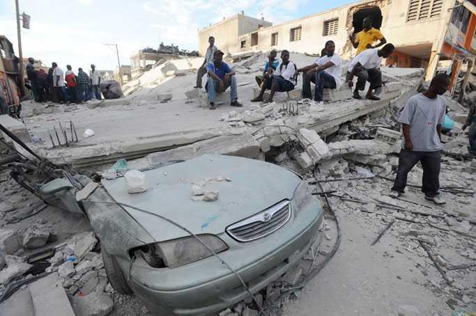 BLAND RASMASSORNA Överlevande sitter på taket till ett raserat hus i Port-au-prince. Över 30 efterskalv har drabbat staden sen det stora jordskalvet – tusentals personer är försvunna.