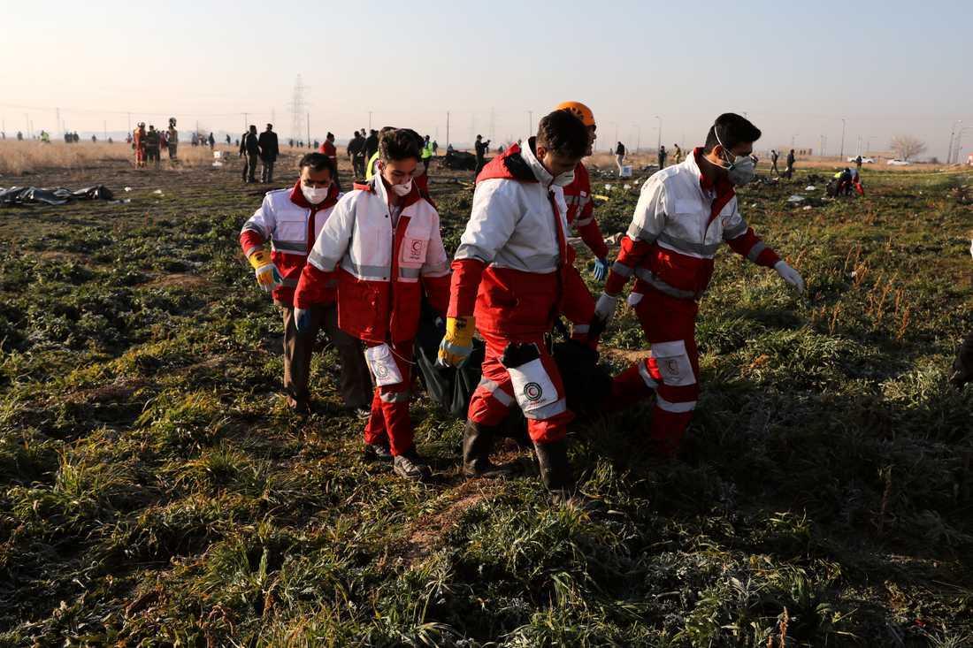 Räddningsarbetare bär bort offren från platsen där det ukrainska planet kraschade i Shahedshahr i Iran.