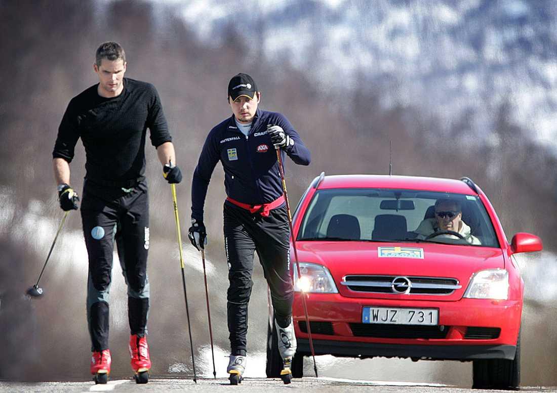 Per Elfosson tränar på rullskidor med sin tränare Thomas Alsgaard Norge, övervakad av förbundskapten Inge Bråten i bilen bakom.