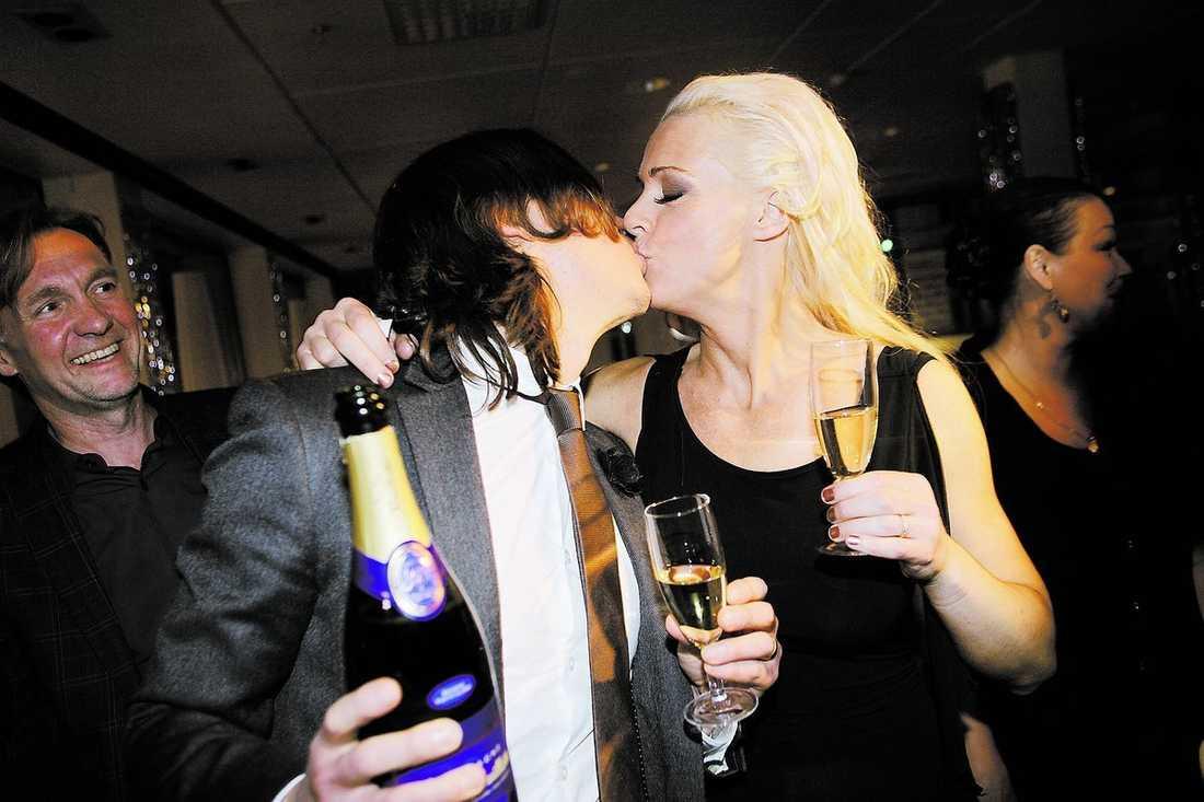 Malena Ernman skålade i champange med sin man Svante Thunberg som bjöd på en riktig segerkyss.