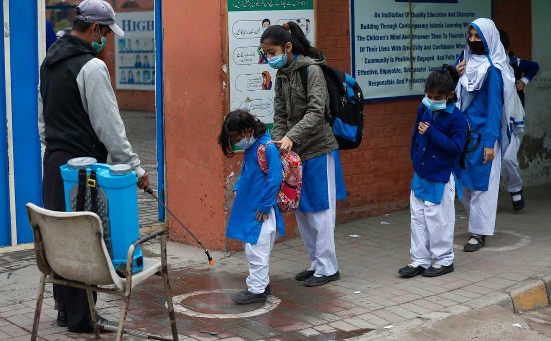 Elever får sina skor desinfekterade i Lahore i Pakistan på onsdagen.