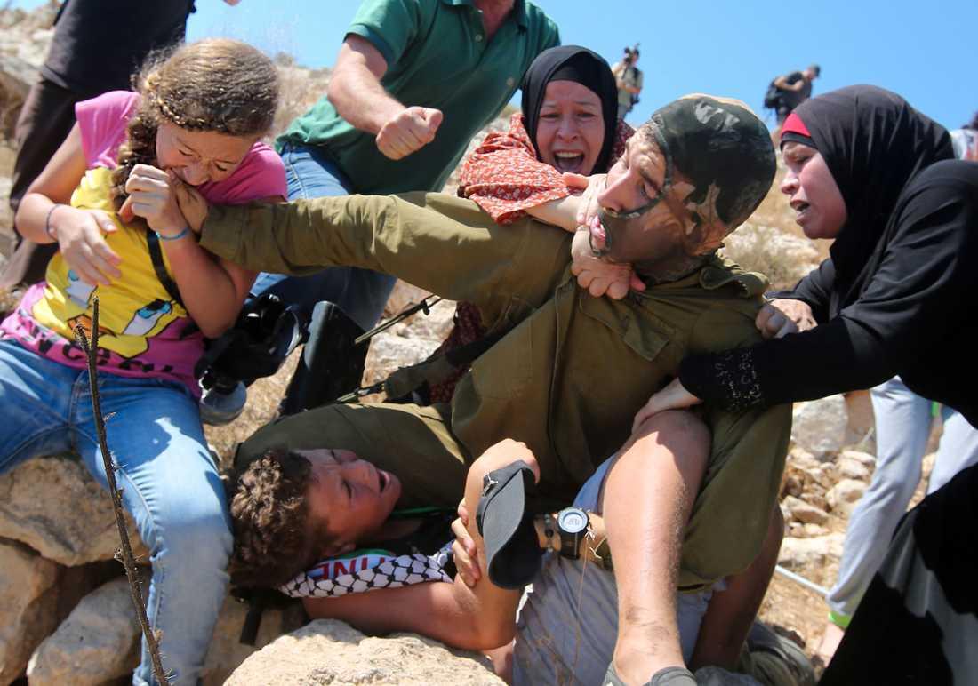 Ahed Tamimi biter en  israelisk soldat i armen.