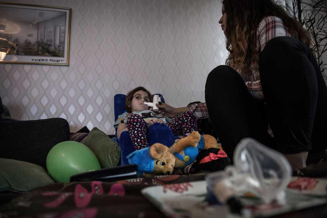 Assistenten Alexandra hjälper Selma med andningsmedicinen.