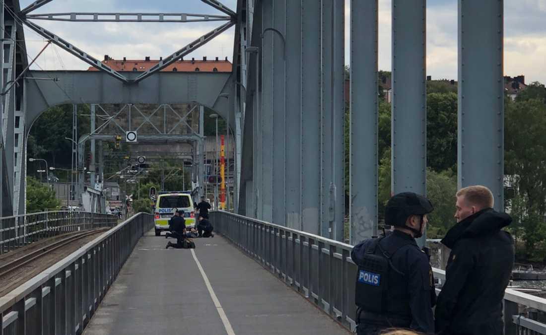Polisen griper en person på bron.