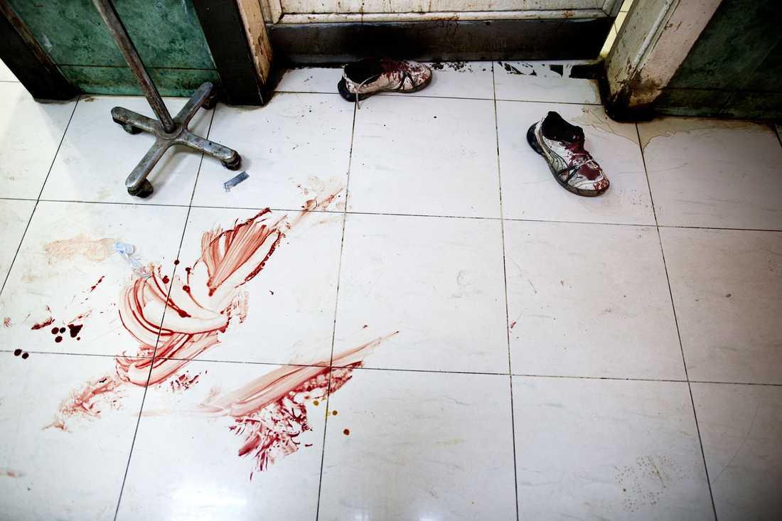 Golvet på Dar al-Shifa-sjukhuset är täckt av blod. Ett par blodiga gympaskor står utanför operationsrummet.