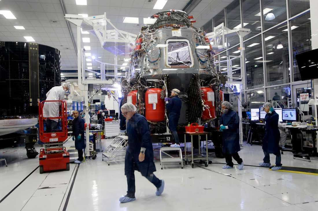SpaceX-anställda runt den Dragon-kapsel som företaget ska använda för resor bland annat till ISS.
