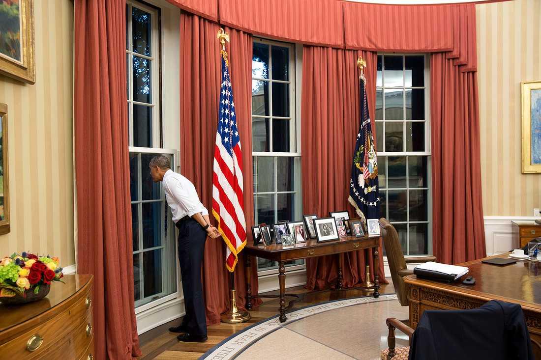 Obama tittar ut genom ett fönster i Ovala rummet samtidigt som en storm passerar utanför.