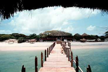 Dugong beach lodge är en av de många lyxiga hotellanläggningarna i Vilanculos coastal wildlife sanctuary. Den privata båtbryggan täcks av ett palmtak.