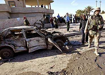 Amerikansk militär bevakar förödelsen utanför polisstationen som attackerades.