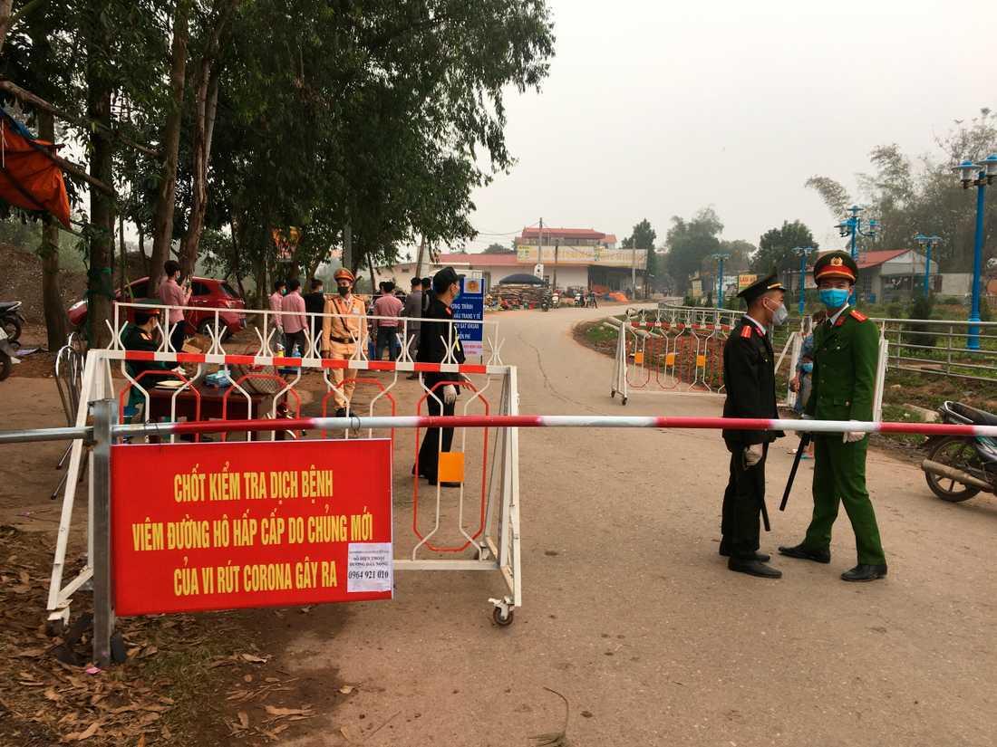 Poliser som bär masker och håller koll vid Son Loi, Vietnam.