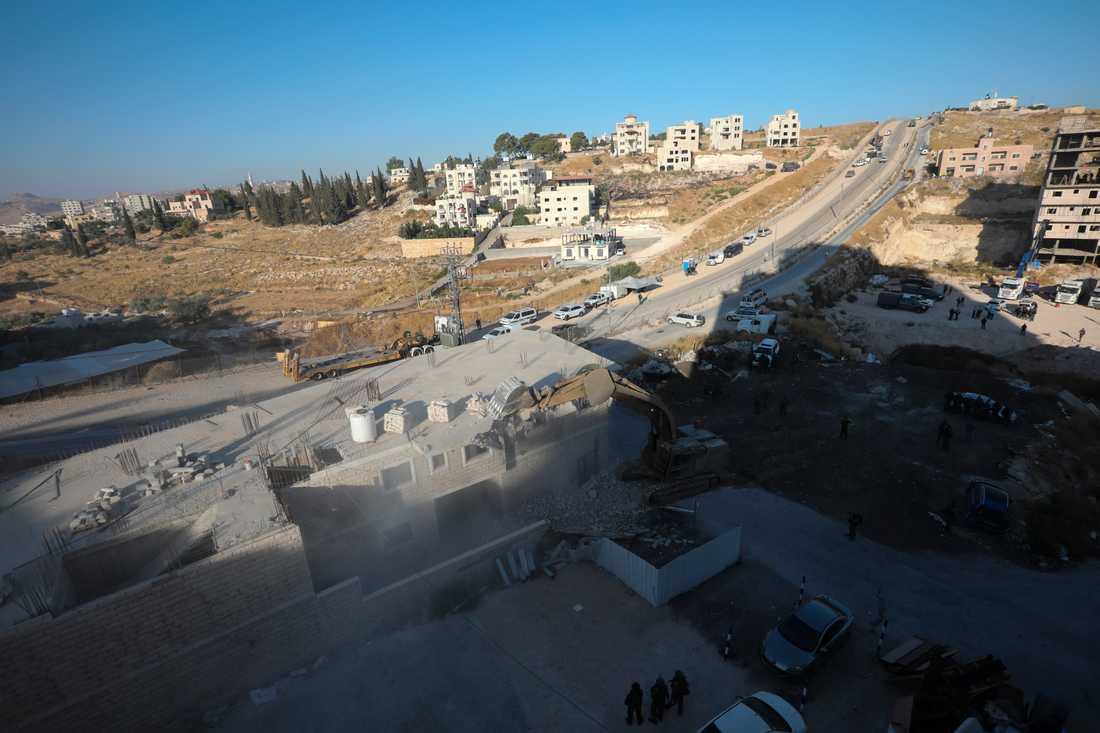 En israelisk militär bulldozer river en byggnad i en palestinsk by söder om Jerusalem.