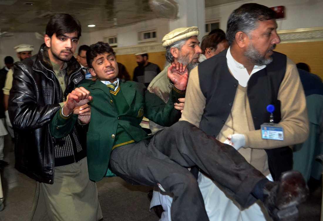 Frivilliga bär iväg en skadad student.