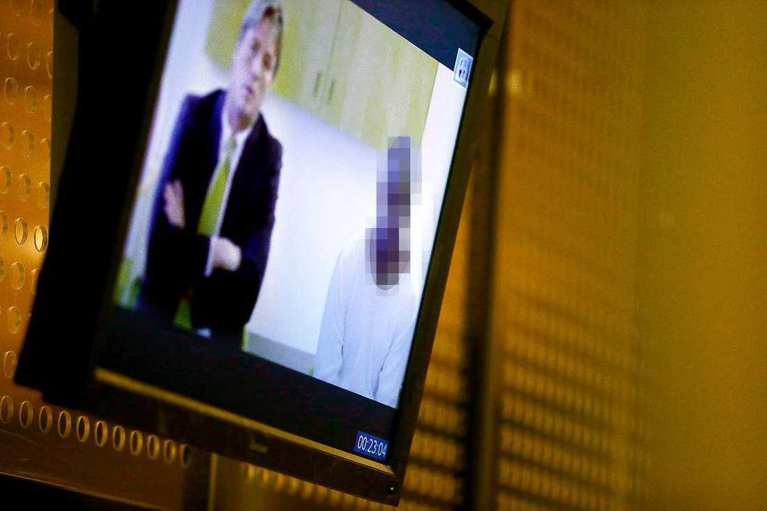 """TV-LÄNK Det ansågs inte """"lämpligt att transportera"""" den anhållne mannen. Han och hans advokat - Thomas Bodström - kommunicerade därför via en videoskärm på väggen."""