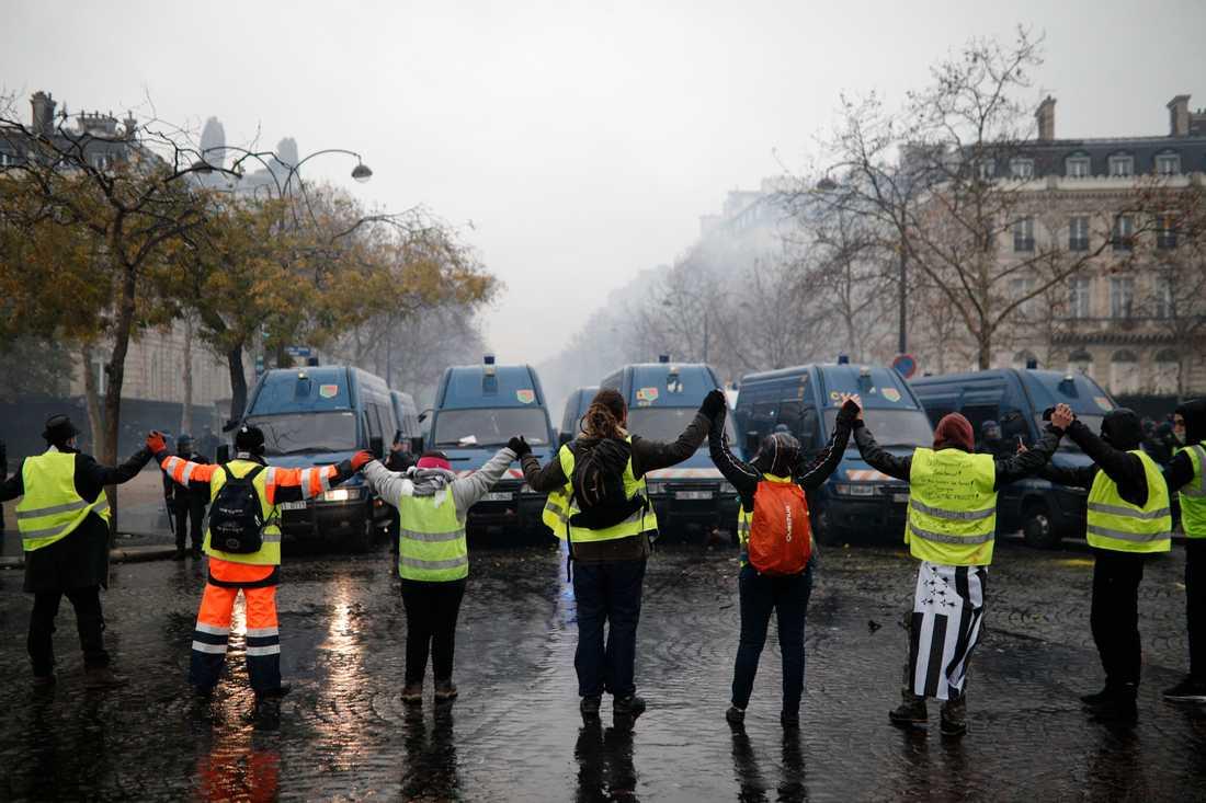 Demonstranter formar en kedja framför polisens ställningar i närheten av Champs-Élysées.