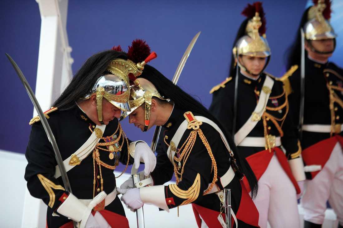En vakt hjälper sin kollega med en kostymdetalj som trasslar.