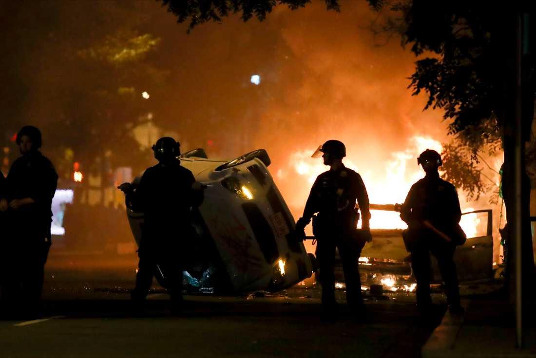 Poliser framför en sönderbränd bil nära Vita Huset där det var våldsamma protester under natten mot måndagen.