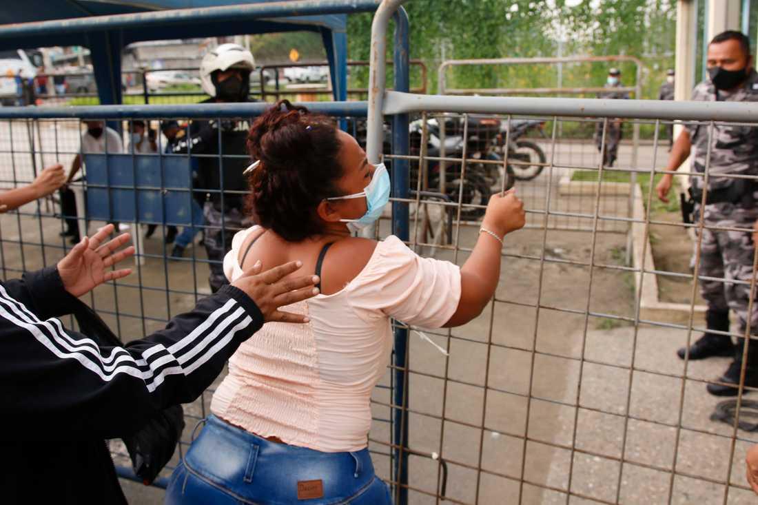 Minst 79 fångar har dödats i bråk mellan gäng i flera fängelser i Ecuador. På bilden en anhörig till en intern utanför säkerhetsfängelset i Guayaquil, där ett av upploppen bröt ut.