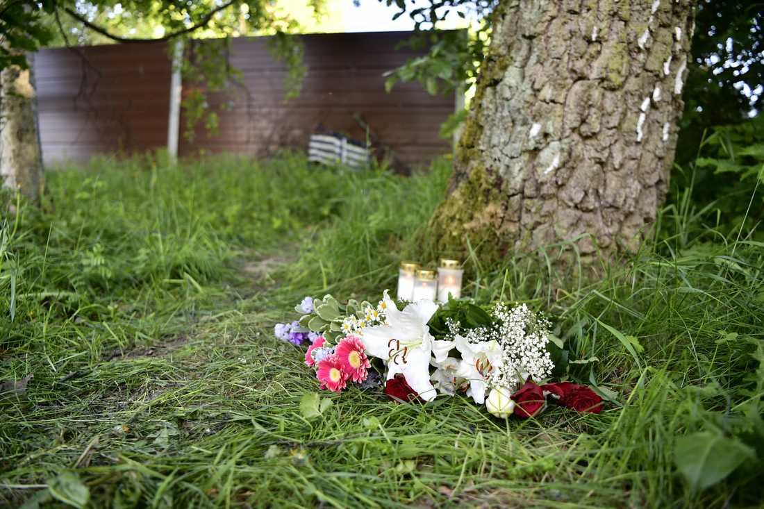 Blommor och ljus på platsen där kroppen hittades.