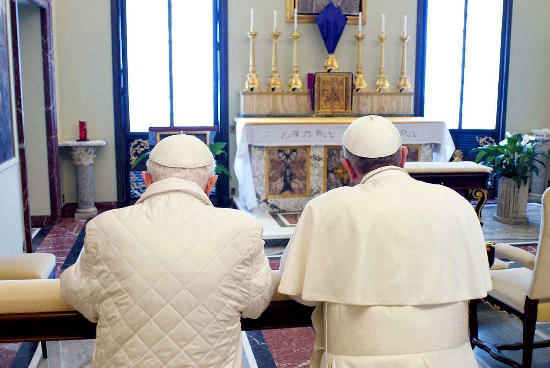 Både gamle påven och påven var helt klädda i vitt. Gamle påven bar en quiltad jacka.