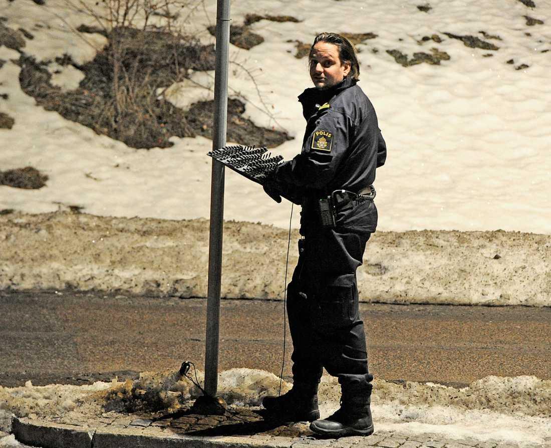 En polis lägger ut en spikmatta.