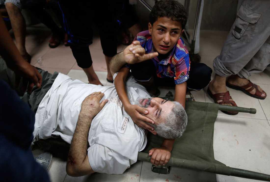 En pojke håller om sin skadade far efter attacken mot marknaden.