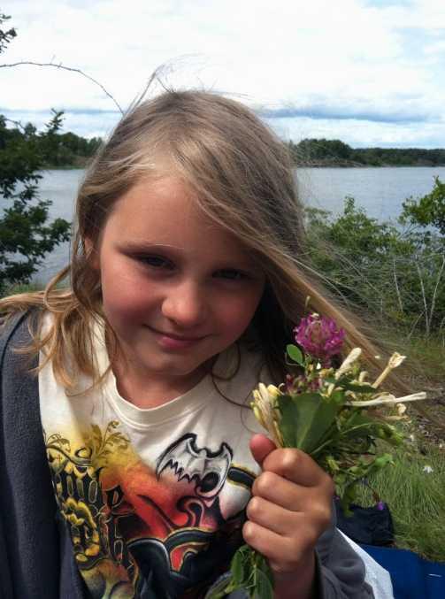 Vilja Brorson, 8, i Karlskrona har plockat sju sorters blommor att lägga under kudden. Hon firar midsommar med familjen.
