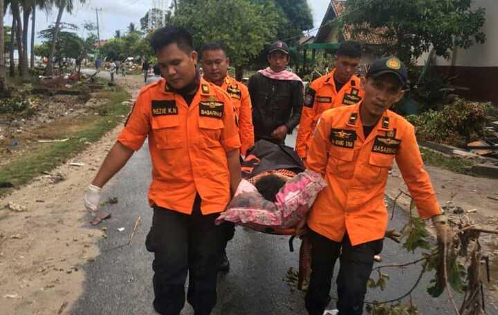Räddningspersonal bär en överlevare på bår. Minst 222 personer har dött efter att en tsunami nådde stränderna vid Sundasundet i Indonesien.