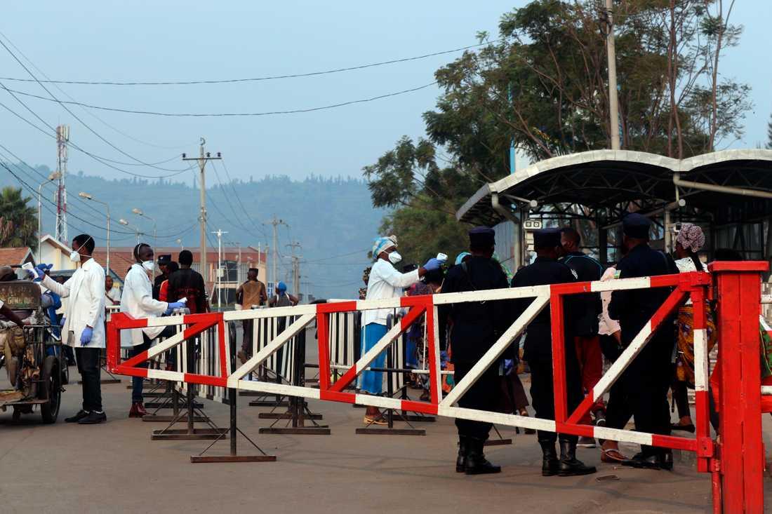 Vårdpersonal kontrollerar personer som korsar gränsen mellan Kongo-Kinshasa och Rwanda.